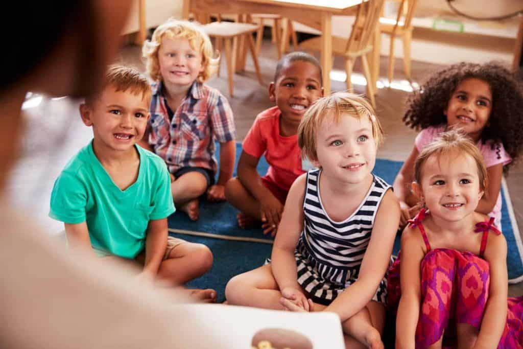 Preschool students smile and listen to their teacher
